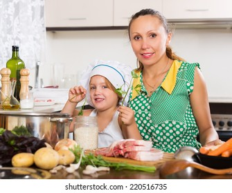 Smiling woman with baby in cook hat cooking with vegetables at kitchen