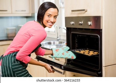 Smiling woman baking biscuits at home