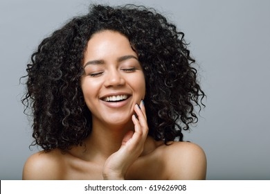 Smiling woman with bare shoulders and closed eyes