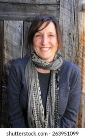 Smiling woman with a barn wood background.