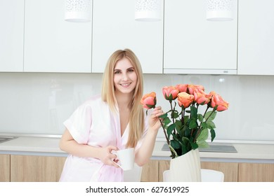 Smiling woman in bathrobe standing with coffee cup at home in the kitchen On the table is a vase with roses