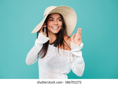 Smiling Woman in beachwear talking on phone and looking away. Isolated turquoise background