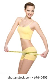 Smiling woman with beautiful body measuring thigh with  measurement type after diet, isolated on white.