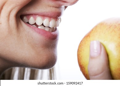 Smiling woman with beautiful teeth about to bite into a ripe juicy apple that she is holding in her hand, close up of her mouth isolated on white