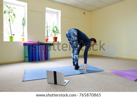 Smiling woman begins on online training with sphinx pose. Girl.