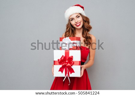 f851041e1602f Smiling woman with big and small gift. Women on dress and santa s hat.  Santa s