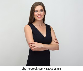 Smiling woman in black dress standing with crossed arms. Isolated one female person.