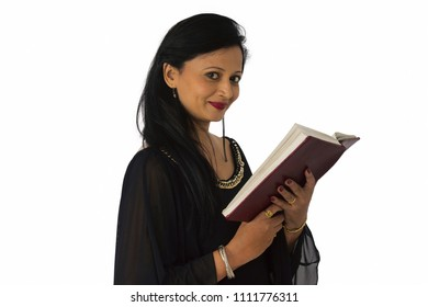 Smiling woman in black salwar suit holding a book. Side pose