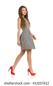 Smiling woman in black and white striped dress and high heels walking and looking at camera, Side view. Full length studio shot isolated on white.