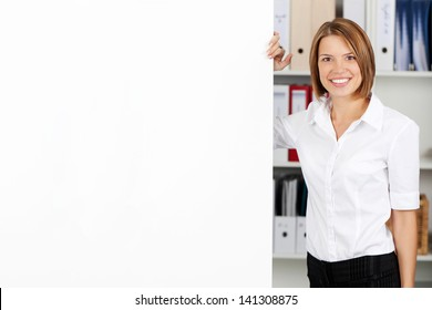 Smiling woman with blank white flipchart while standing alongside it in the office