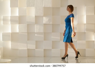 Smiling woman in blue dress walking against modern wall with wallet in hand