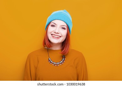 Smiling woman in blue hat looking at the camera on yellow background