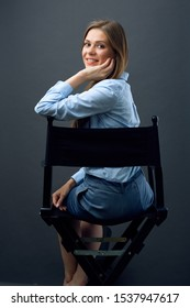 smiling woman boss sitting back on black movies director chair turns away to side. isolated female profile portrait.