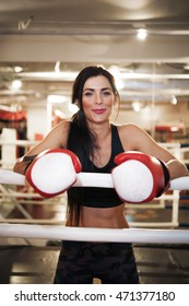 Smiling woman in boxing gloves at ring
