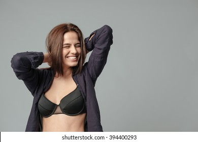 Smiling woman in bra posing over gray background