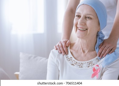 Smiling woman with breast cancer wearing pink ribbon on chest