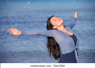 Smiling woman breathing with sea in the background