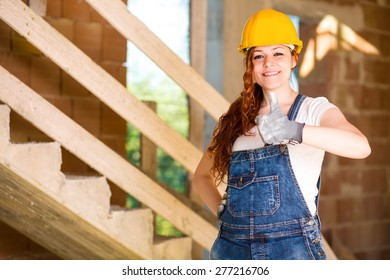 Smiling Woman Bricklayer with Overalls and Helmet Thumbs Up