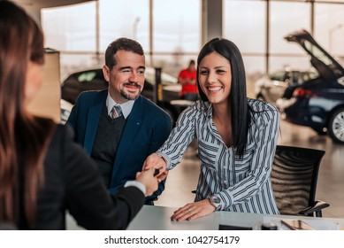 Smiling woman buying car at showroom. Car saleswoman and customer handshake.
