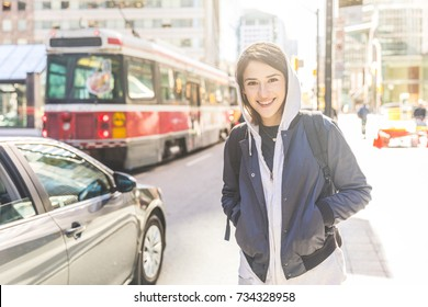 Smiling woman by the street in the city. Portrait of a young woman with short hair, wearing a hoodie and jacket, walking next to a busy road in Toronto. Travel and lifestyle concepts.