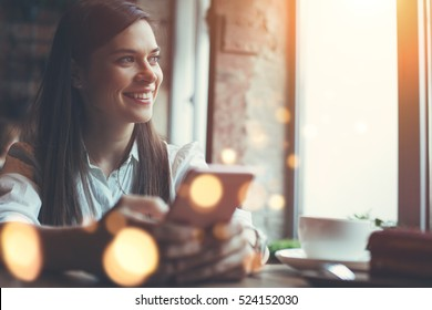 Smiling woman in cafe using mobile phone and texting in social networks, sitting alone
