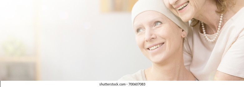 Smiling woman with cancer hugged by mother
