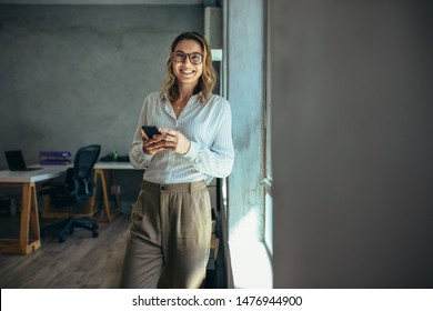 Smiling woman in casuals standing in office. Businesswoman with mobile phone in hand looking at camera. - Shutterstock ID 1476944900