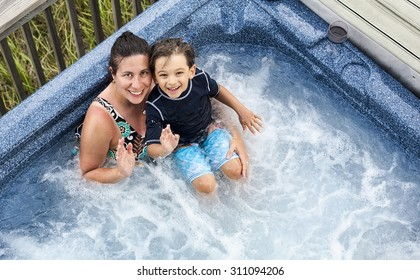 A smiling woman and child waving to the camera from a hot tub