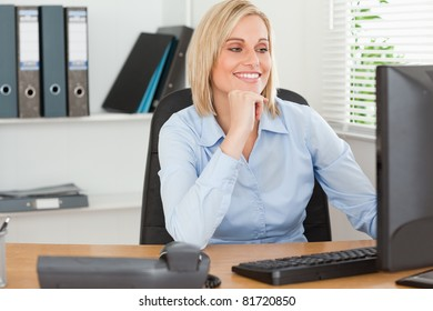 Smiling woman with chin on hand behind a desk looking at screen in an office