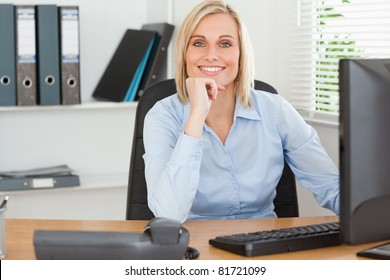 Smiling woman with chin on hand behind a desk in an office