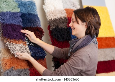 Smiling woman choosing carpet samples from a colorful display on the wall of a retail shop