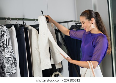 Smiling woman choosing jacket at the clothing store