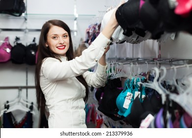 Smiling woman choosing underwear at clothing store