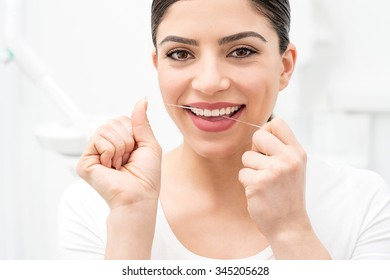 Smiling woman cleaning her teeth