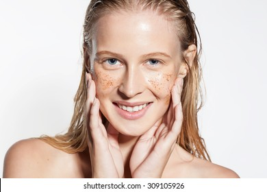 Smiling woman cleans the skin coffee scrub