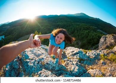 笑顔の女性が石に登りつめている。親しみやすい手助け。相手が女の子の山登りを手伝う。チームワーク。日没に登る。