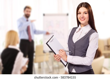 Smiling woman with clipboard in office during meeting
