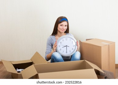 Smiling woman with the clock sitting on the floor among the moving boxes