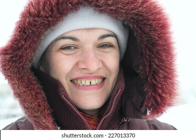 Smiling woman closeup portrait in her 40's in winter clothes, winter walking in warm clothing, happy living person