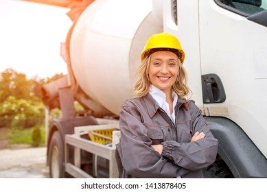 Smiling woman, concrete truck driver, with safety helmet standing in front of  the truck