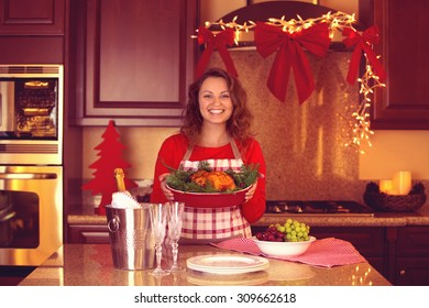 Smiling woman cooking festive thanksgiving dinner at home. Posing with chicken at the kitchen, with Christmas festive light background