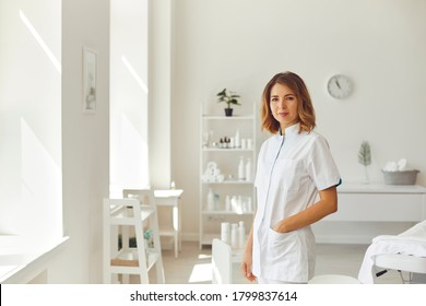 Smiling woman cosmetologist or dermatologist standing and looking at camera in beauty spa salon