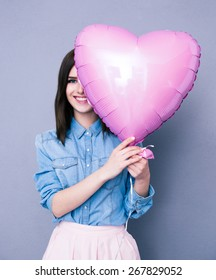 Smiling woman covering her eye with heart shaped balloon over gray background. Looking at camera