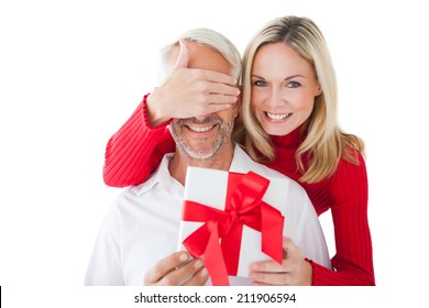 Smiling woman covering partners eyes and holding gift on white background