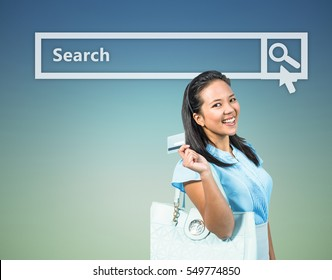 Smiling woman with a credit card in hand against dark blue green background