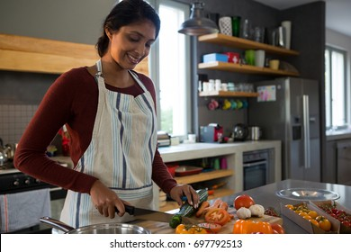 Smiling woman cutting zucchini in kitchen at home