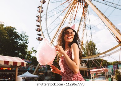 Smiling woman with dark curly hair in sunglasses and birthday cap standing with cotton candy in hand and happily looking aside while spending time in amusement park with ferris wheel on background