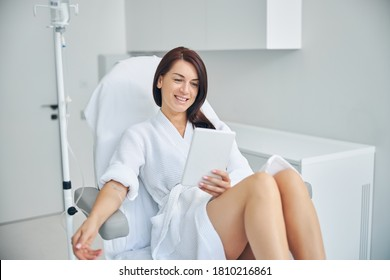 Smiling woman with dark hair getting an intravenous vitamin drip treatment at a beauty salon