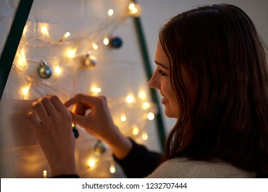 smiling woman decorating for festive season, fairy lights on creative christmas tree made with washi tape