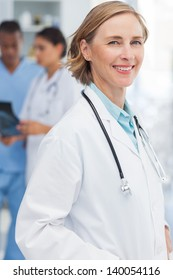 Smiling woman doctor standing in front of medical team
